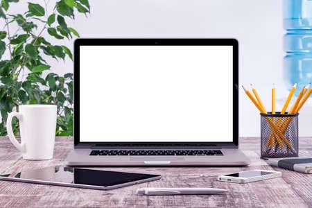trabajando en computadora: Lugar de trabajo de oficina con computadora tablet maqueta abierta portátil y el teléfono inteligente en el escritorio de madera. Para la presentación de diseño o cartera. Todos los dispositivos de atención plena.