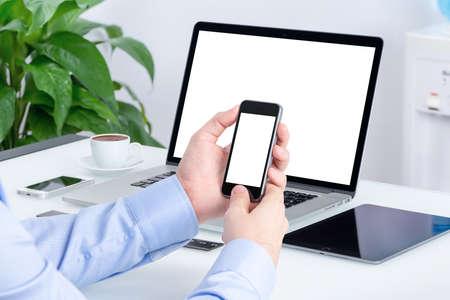 mecanografía: Manos masculinas utilizando maqueta smartphone con pantalla en blanco en el escritorio de oficina con una maqueta portátil abierto y tablet PC. Todos los dispositivos de atención plena. Para la presentación de diseño de respuesta. Foto de archivo