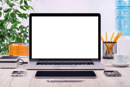 Lugar de trabajo con maqueta portátil abierto diferentes aparatos y equipos de oficina en el escritorio. Para la presentación de diseño o cartera. Todos los dispositivos en foco.