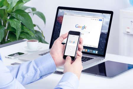 Google-zoekopdracht op Apple iPhone-scherm en Macbook Pro Retina-display dat op kantoor bureau. Multi-apparaten multitasking concept. Alle gadgets in volle focus. Varna, Bulgarije - 29 mei 2015.