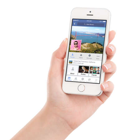 5s: Female hand holding Apple Silver iPhone 5S with Facebook application on the screen. Facebook is an online social networking service. Isolated on white background. Varna, Bulgaria - February 02, 2015. Editorial