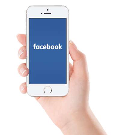 Vrouwelijke hand die Apple zilveren iPhone 5S met Facebook nieuwe logo op het scherm. Facebook is een online social networking service. Geïsoleerd op een witte achtergrond. Varna, Bulgarije - 2 februari 2015.