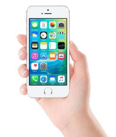 iOS 9 homescreen op de witte Apple iPhone 5s vertoning in vrouwelijke hand. iOS 9 is een mobiele besturingssysteem gecreëerd en ontwikkeld door Apple Inc. geïsoleerd op een witte achtergrond. Bulgarije - 2 februari 2015.