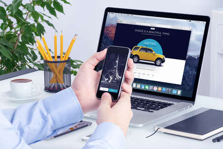 Uber application on the Apple iPhone display and desktop version of Uber on the Apple Macbook Pro screen. Uber multi devices concept. All gadgets in full focus. Varna, Bulgaria - May 29, 2015. Editoriali