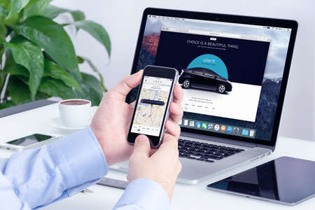 Varna, Bulgaria - May 29, 2015: Man orders Uber X through his iPhone and Macbook with Uber website on the background. Uber Technologies Inc. is an American international transportation network company.