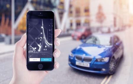 Varna, Bulgaria - May 25, 2015: Uber application startup page on the Apple iPhone 5s display in female hand. Blurred street view with car and flare sun light on the background.