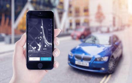 Varna, Bulgarije - 25 mei 2015: Uber applicatie opstarten pagina op de Apple iPhone 5s vertoning in vrouwelijke hand. Wazig uitzicht op straat met de auto en flare zonlicht op de achtergrond. Redactioneel