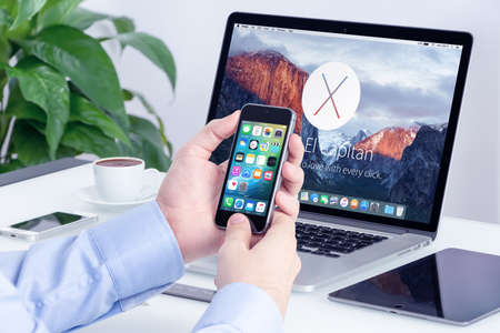 Apple MacBook Pro Retina with announced on WWDC 2015 OS X El Capitan on the screen and Apple iPhone 5s with iOS 9 on the display in male hands in office workspace. Varna, Bulgaria - May 29, 2015. Editoriali