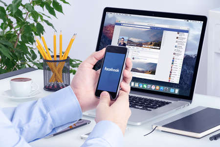 Facebook app on the Apple iPhone display and desktop version of Facebook on the Apple Macbook Pro Retina. Multi devices multitasking concept. All gadgets in full focus. Varna, Bulgaria - May 29, 2015. Editoriali