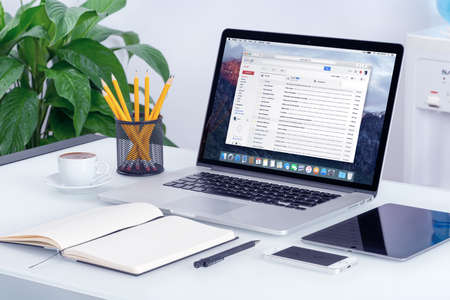 Varna, Bulgaria - May 29, 2015: Google Gmail email inbox interface on the Apple MacBook Pro screen that is on office desk. Gmail is a free email service provided by Google. All gadgets in focus.