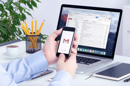 correo electronico: Varna, Bulgaria - 29 de mayo 2015: Gmail app en la pantalla del iPhone en las manos del hombre y la versión de escritorio de Gmail en la pantalla Macbook. Gmail es un servicio de correo electrónico gratuito proporcionado por Google. Todos los aparatos en el enfoque.
