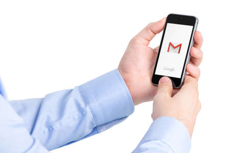 webmail: Varna, Bulgaria - May 29, 2015: Man holding Apple iPhone with Google Gmail application logo on the screen. Gmail is a most popular free Internet e-mail service provided by Google. Isolated on white.