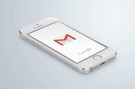 gmail: Varna, Bulgaria - May 31, 2015: Google Gmail app logo on the white Apple iPhone 5s display that lies on the surface. Gmail is a free e-mail service provided by Google. Isolated on white background.