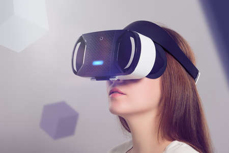 presence: Woman in VR headset looking up at the objects in virtual reality. VR is a computer technology that simulates a physical presence and allows the user to interact with environment.
