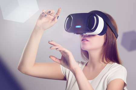Woman in VR headset looking up and trying to touch objects in virtual reality. VR is a computer technology that simulates a physical presence and allows the user to interact with environment. Archivio Fotografico