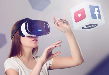 virtual reality simulator: Varna, Bulgaria - March 10, 2016: Woman in VR headset looking up and interacting with Facebook Youtube Steam VR content. Facebook Google & Steam believes that VR is the future of content consumption. Editorial