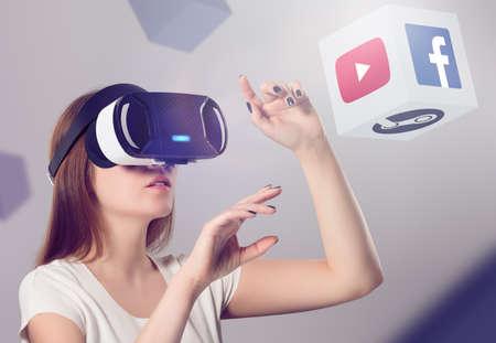 Varna, Bulgarije - 10 maart 2016: Vrouw in de VR-headset te kijken en interactie met Facebook Youtube Steam VR content. Facebook Google & Steam gelooft dat VR is de toekomst van de inhoud consumptie.