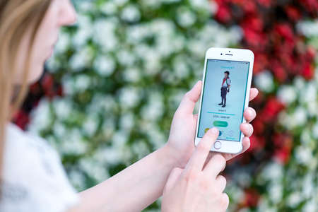 Varna, Bulgaria - Jul 19, 2016: Nintendo Pokemon Go augmented reality mobile application profile page with game character on Apple iPhone 6S in female hands. Blurred flowers view on the background.