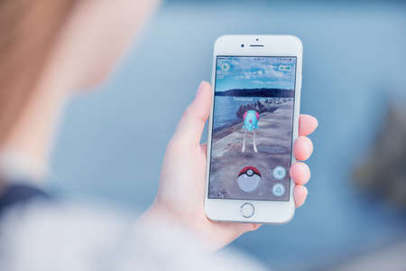 nintendo: Varna, Bulgaria - Jul 19, 2016: Nintendo Pokemon Go augmented reality mobile application game with Tentacool pokemon catching on Apple iPhone 6S in female hand. Blurred view on the background.