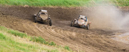 fourwheeldrive: Competition. Buggy racing on a dirt road. Water splashing from the wheels.