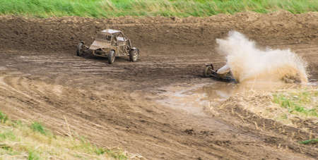 Competition. Buggy racing on a dirt road. Water splashing from the wheels.