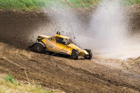 Competition. Buggy racing on a dirt road. Dirt from the wheels. Water splashing from the wheels. Stock Photo