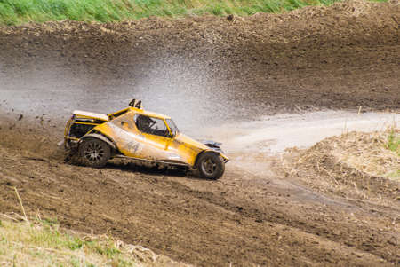 fourwheeldrive: Competition. Buggy racing on a dirt road. Dirt from the wheels. Water splashing from the wheels. Stock Photo