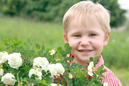 Happy boy smiles near the flowers