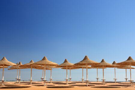 cielo azul y sombrillas en la playa