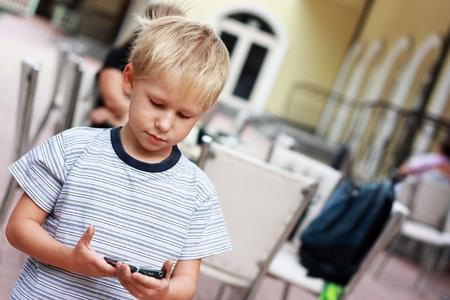 El chico ley� un mensaje SMS al tel�fono m�vil Foto de archivo