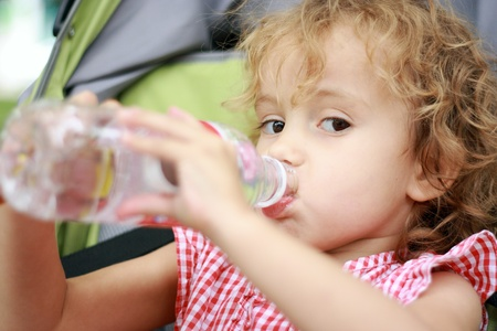 Beautiful girl seat in pram and is drinking water from plastic bottle.