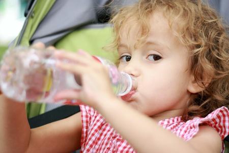 Hermosa ni�a de asientos en el cochecito y se bebe el agua de la botella de pl�stico.