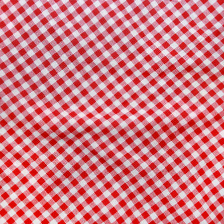 Abstract texture of a red and white checkered picnic blanket.