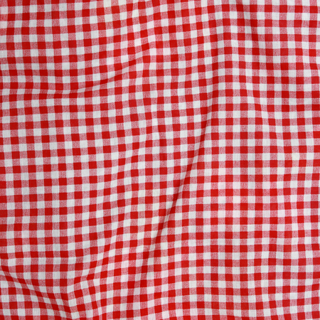Abstract background texture of a red and white checkered picnic blanket. Red linen crumpled tablecloth.