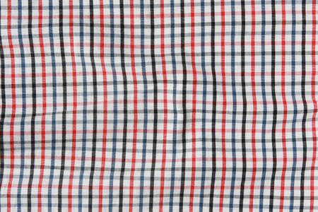 Texture of a red and white checkered picnic blanket. Striped crumpled tablecloth.  Stock Photo