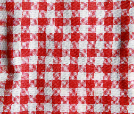 Texture of a red and white checkered picnic blanket. Red linen crumpled tablecloth.  Stock Photo