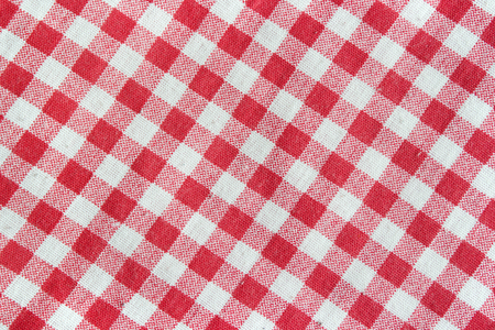 Texture of a red and white checkered tablecloth. Red linen crumpled picnic blanket.