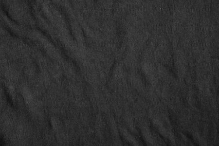 black fabric: Black canvas with delicate striped pattern, crumpled. Fabric texture.