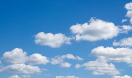 over the horizon: White clouds flying against blue sky. Beautiful cloudscape over horizon.