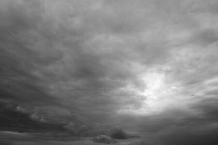 over the horizon: Sunshine through storm sky, clouds. Thunderclouds over horizon, dark, gray. Stock Photo