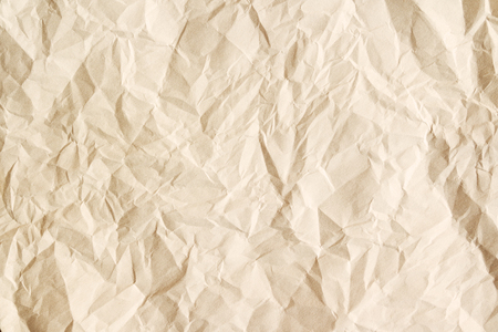 Old crumpled parchment texture. Beige aged paper sheet background.