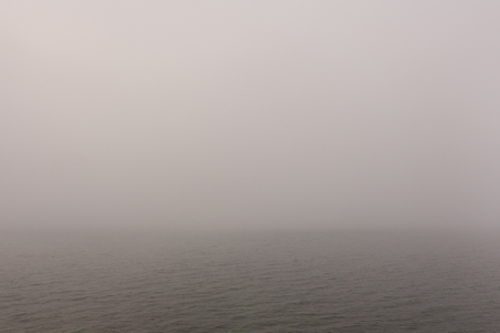 Heavy fog over morning calm water surface.