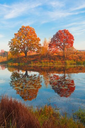 Beautiful autumn landscape, forest lake with reflection. Beautiful autumn, sunset over forest calm lake, pond.