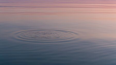 Sunset reflected in calm mirrored water surface.