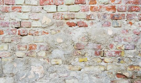 Background of old brick wall partly covered by concrete
