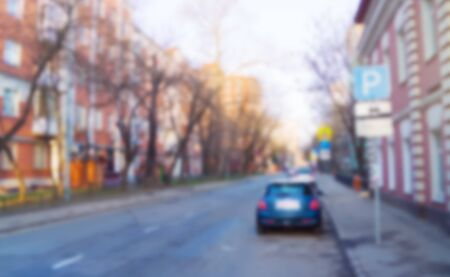 Blurred street in sunlight, urban scene with parking sign and one auto
