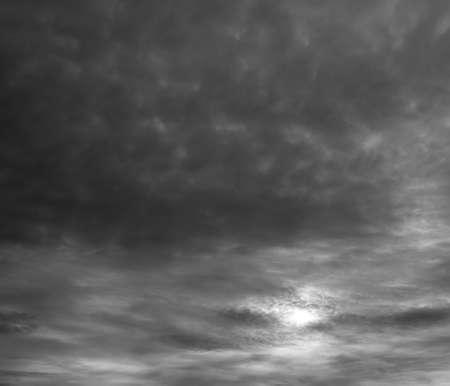 Dramatic gray clouds, sun shine through stormy clouds. 版權商用圖片