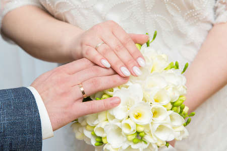 hands of newlyweds in wedding rings against the background of the wedding bouquet