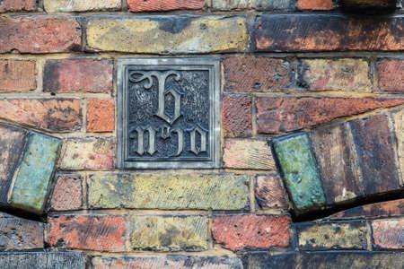 wall decor: Art decor plate on old brickwork wall in Brugge, Belgium