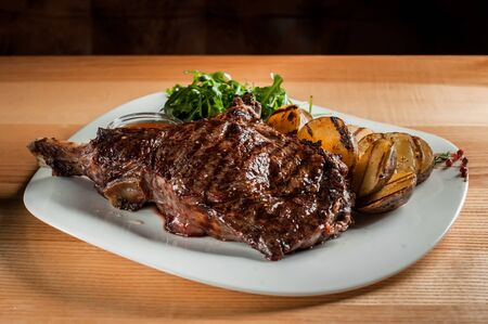 A beautiful juicy steak with salad on plate is on the wooden table. Stock Photo